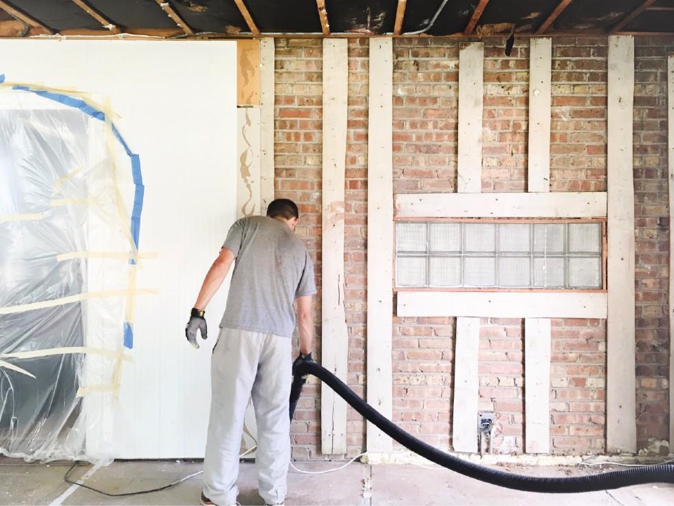 person som dammsuger ett rum som just nu renoveras. Det är tegelväggar och plastskynke över dörröppningen